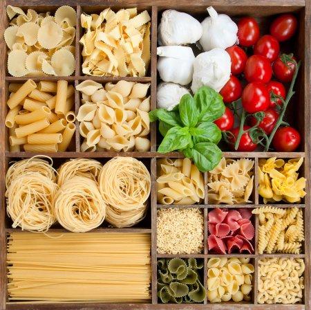 Photo pour Assortiment de pâtes dans une boîte en bois avec des ingrédients de cuisine - image libre de droit