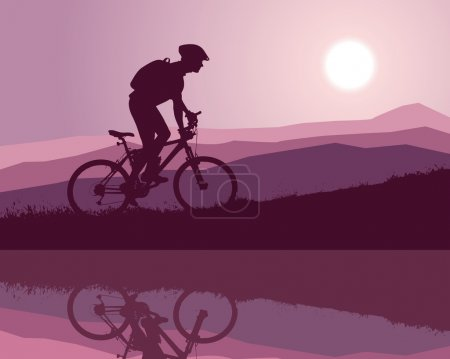 Cyclist on a mountain bike riding along a mountain lake early in the morning