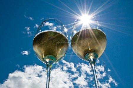 Photo pour Gros plan de deux verres à vin avec un éclat de soleil rempli de vin blanc côte à côte avec ciel bleu vif et nuages en arrière-plan - image libre de droit