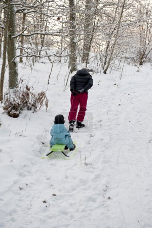 Mother pulling snow sledge up a hillside