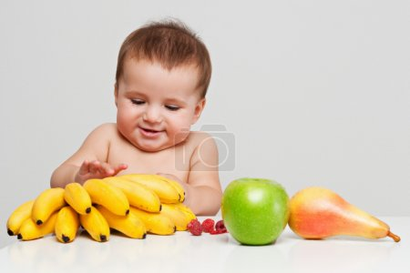 Happy baby with fruits