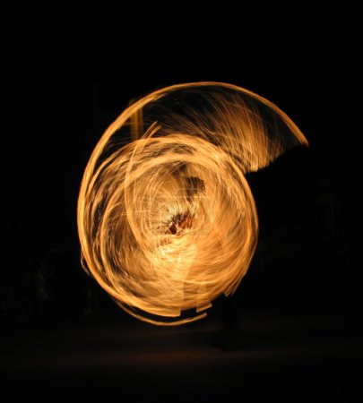 Girl performing fire dance in the night; silhouette