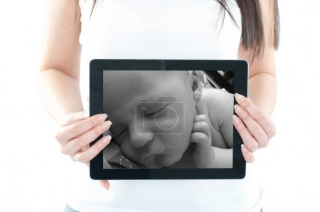 Expectant mother is holding tablet pc with ultraso...