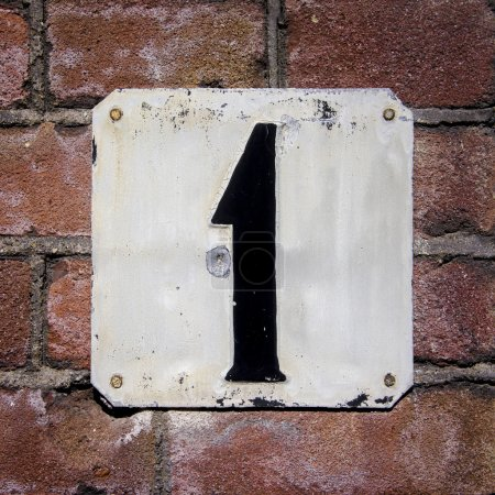 Photo for Weathered and cracled house number one on a brick wall - Royalty Free Image