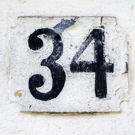 Photo pour Maison altérée numéro 34. Fonte noire sur fond blanc - image libre de droit