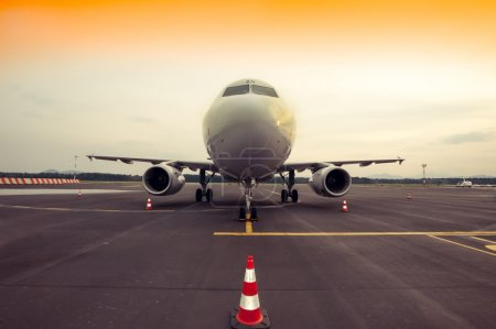 Commercial airplane parking at the airport, with traffic cone in