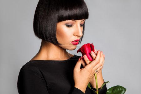 Beauty adult girl with red rose looking down in studio on gray b