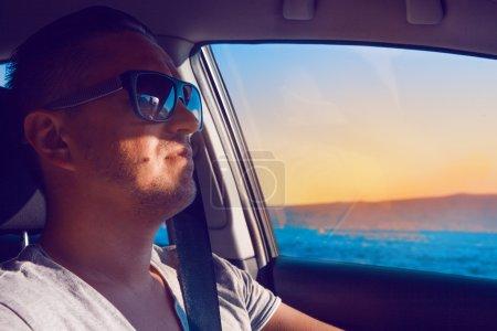 Elegant caucasian male driving car near sea