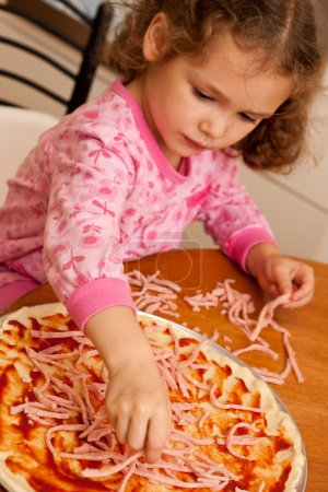Girl child cooking homemade pizza in kitchen