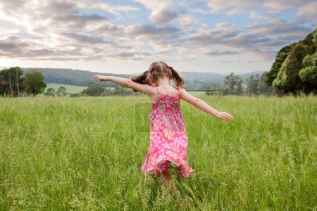 Girl running through long grass