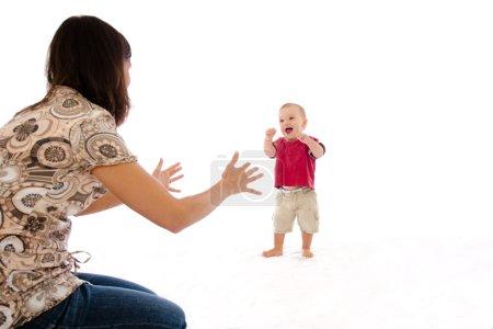 Photo pour Mère tenant les bras au bébé souriant pour faire ses premiers pas - image libre de droit