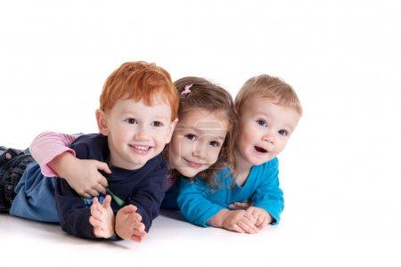 Three happy kids on floor together