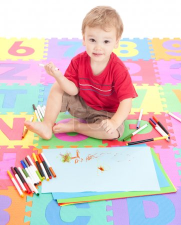 Boy child drawing on kids mat