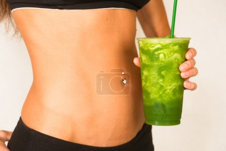 Woman holds Green Fruit Smoothie Waist Level Showi...