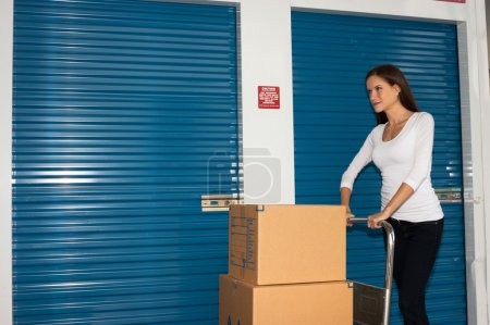 Photo for Smiling woman carts boxes through storage facilty - Royalty Free Image