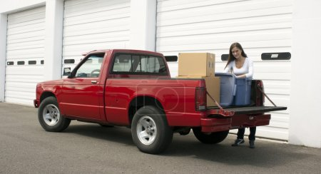 Photo for Woman gets out of truck to unload at storage location - Royalty Free Image