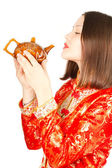 Asian woman drinking Chinese tea from the teapot in Kimono on a white backg