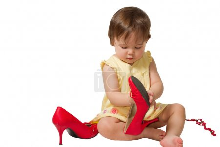 Little girl-child trying on mother s big red shoes on a white background