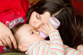 Young mother feeds child girl with a bottle with infant formula on bad. The