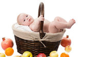 baby girl in a basket with fruits isolated on white background The concept of childhood and holiday