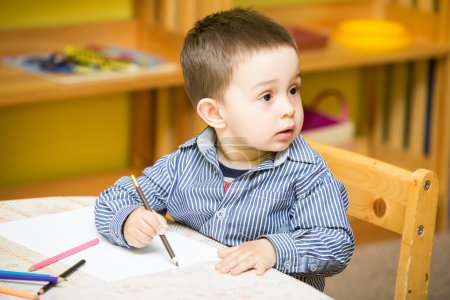 Little child boy drawing with colorful pencils