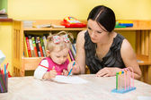 Mother and child girl playing in kindergarten in Montessori preschool Class.