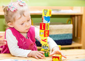 Little child girl playing with toy letter and number blocks  in kindergarten in Montessori preschool Class.