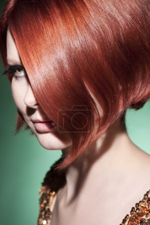 Portrait of young beautiful girl with red hair on a green background