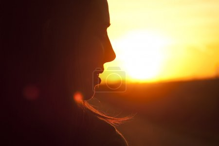Beautiful and happy woman in front of sunrise background