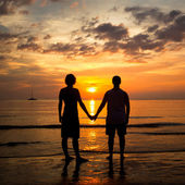 Young couple holding hands on the sea beach at sunset