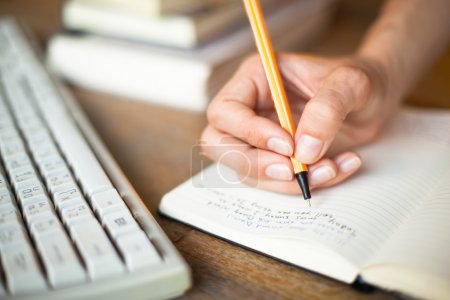 Photo for Photo of hands writes a pen in a notebook, computer keyboard and a stack of books in background - Royalty Free Image