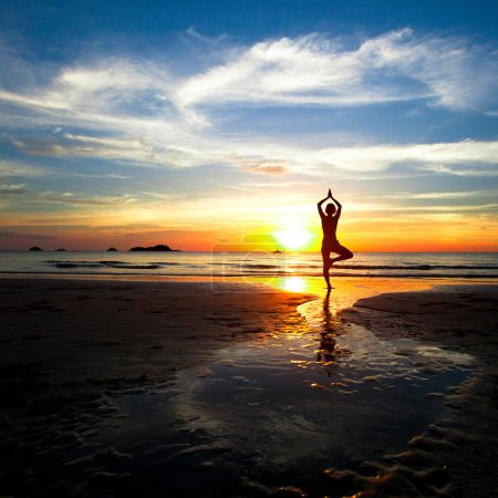 Photo for Silhouette of woman practicing yoga on the beach during a beautiful sunset. - Royalty Free Image