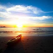 Kayak on the beach at sunset.