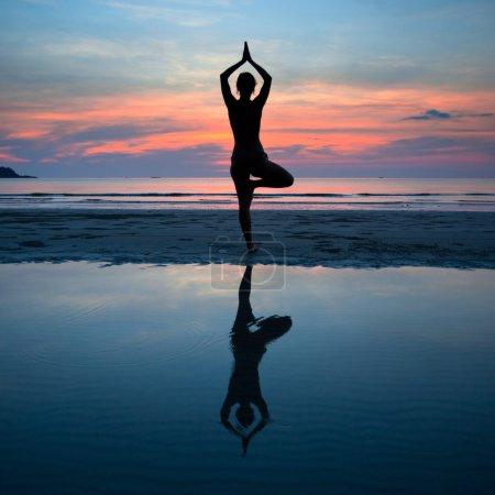 Jeune femme pratiquant le yoga au coucher du soleil sur la côte, avec le reflet dans l'eau