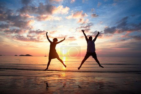 Photo for Concept of long-awaited vacation: Young couple in a jump on the sea beach at sunset. - Royalty Free Image