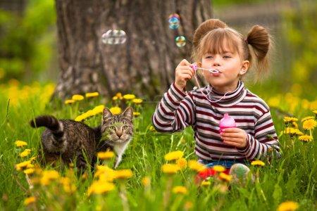 Photo pour Drôle belle petite fille et un chat, en soufflant des bulles de savon - image libre de droit