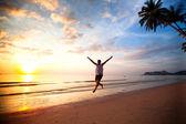 Young fun man running on sea beach at sunset