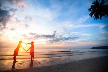 Young couple holding hands heart-shaped on the sea beach at sunset.