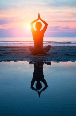 Photo for Young woman practicing yoga on the beach at sunset (with reflection in water) - Royalty Free Image