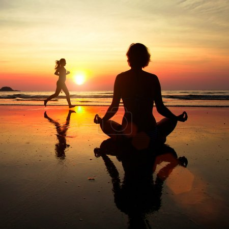 Concept of healthy lifestyle: Silhouette of a woman meditating on the beach at sunset.