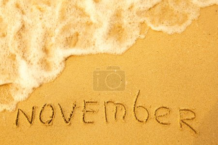 November - written in sand on beach texture