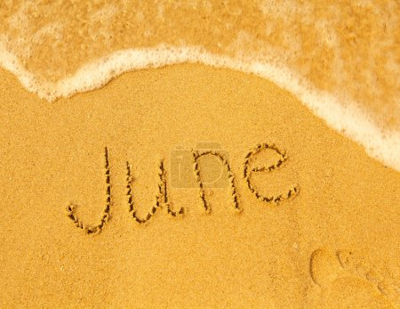 June - written in sand on beach texture