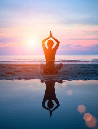 Silhouette d'une femme yoga sur le coucher de soleil de mer avec réflexion dans l'eau .
