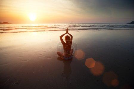 Yoga woman sitting on sea coast at sunset