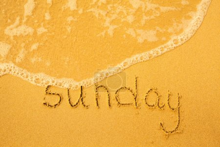 Sunday - written in sand on beach texture - soft wave of the sea (days week series)