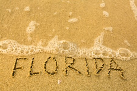 Florida - written in sand on beach texture - soft wave of the sea.