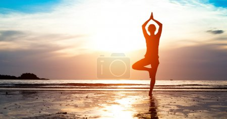 Silhouette young woman practicing yoga on the beach