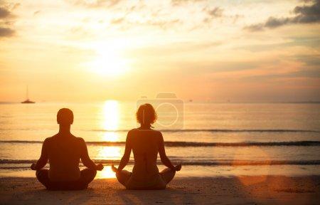Photo pour Un jeune couple assis sur la plage de la mer dans la position du lotus au coucher du soleil, pratique du yoga - image libre de droit
