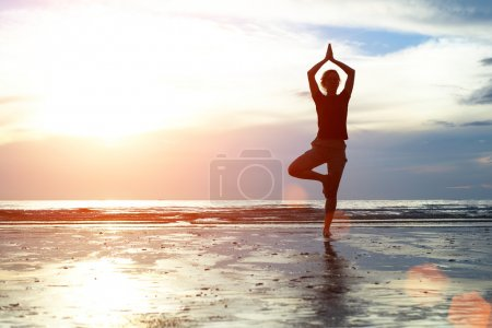 Practicing yoga on the beach at sunset