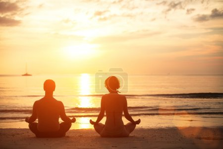 Photo for Young couple sitting on the beach of the sea in the lotus position at sunset, yoga practice - Royalty Free Image
